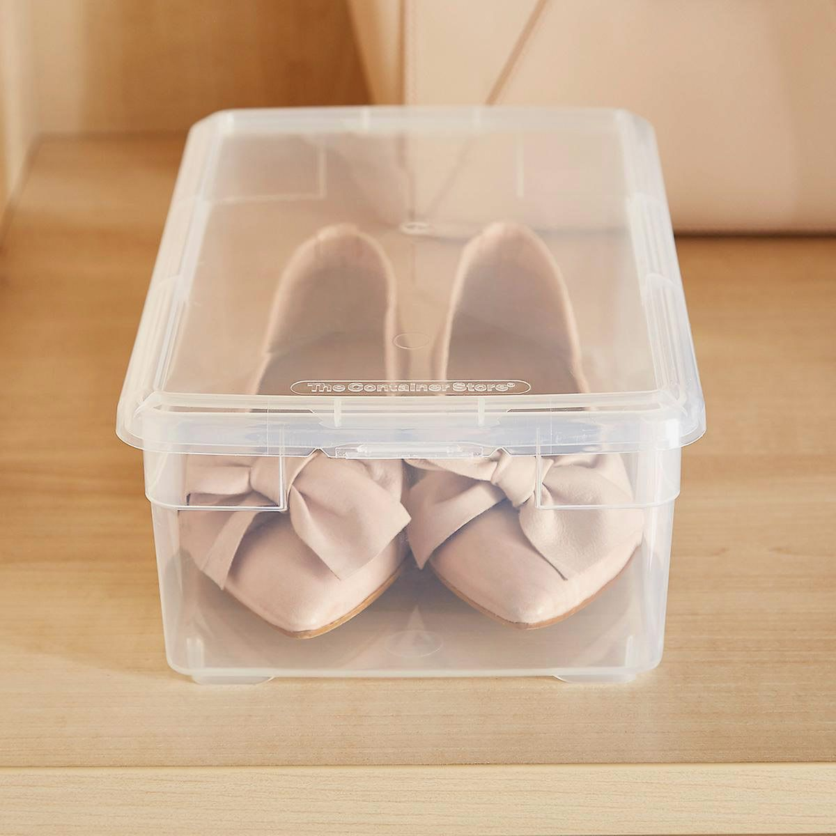 Pink flat shoes in a clear plastic box.
