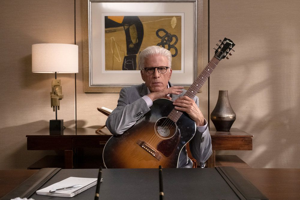 """Michael (Ted Danson) rests his chin on a guitar in a screenshot from The Good Place season 4, episode 13 """"Whenever You're Ready"""""""