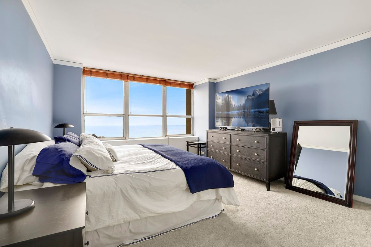 A room with blue walls. There is a bed one one side of the room and a dresser topped by a TV at the other. The far wall has a large window overlooking a body of water.