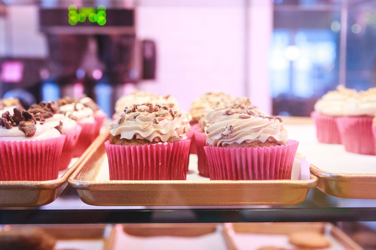 Rows of frosted cupcakes in pink paper sit on a tray inside a pastry case.