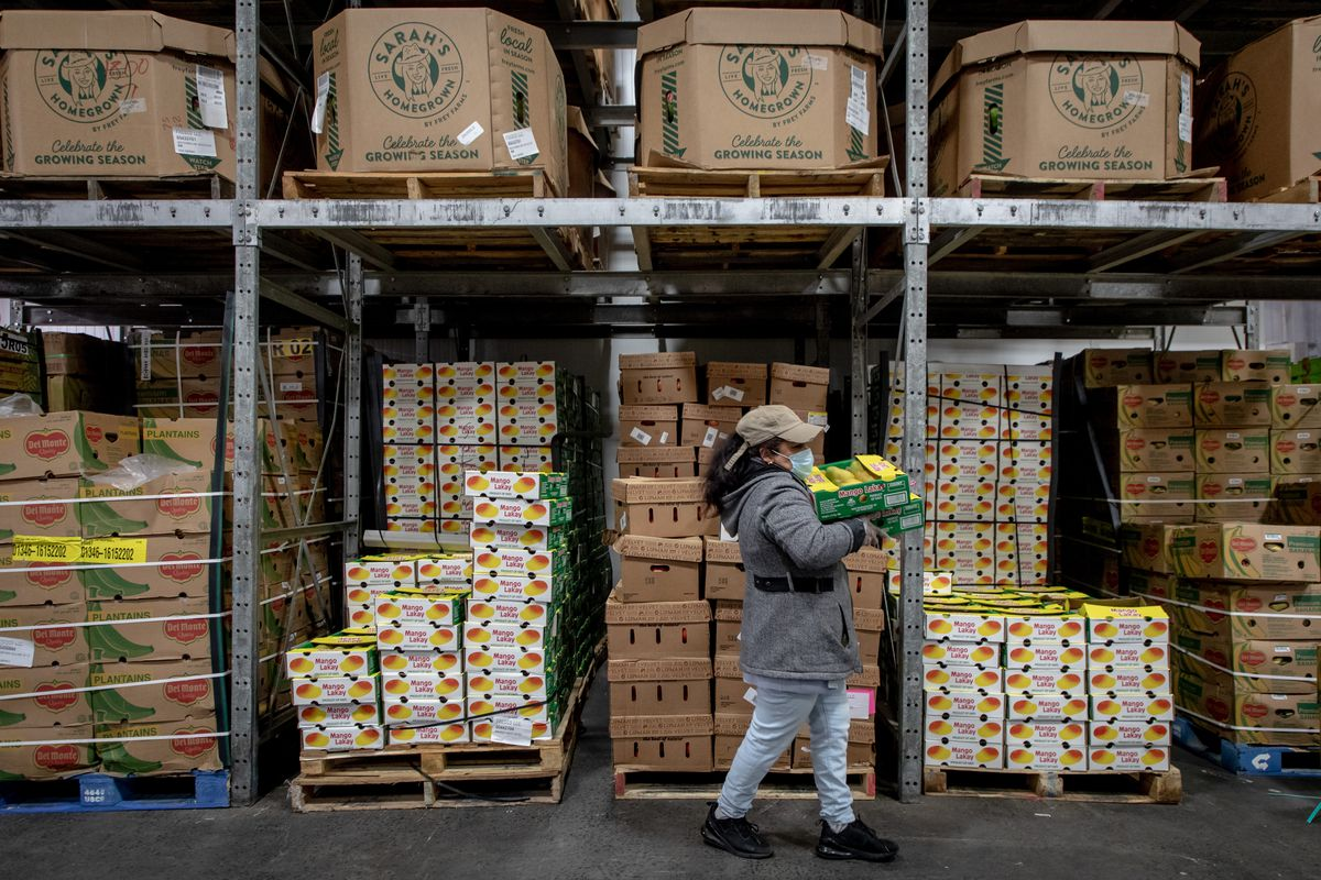 A street vendor moves boxes of produce inside a warehouse