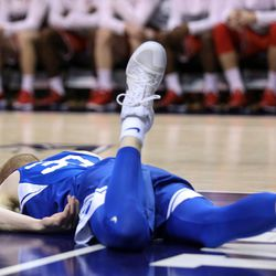 Brigham Young Cougars guard TJ Haws (30) lays on the court after falling hard on the boards during the game against the Utah Utes at the Marriott Center in Provo on Saturday, Dec. 16, 2017.