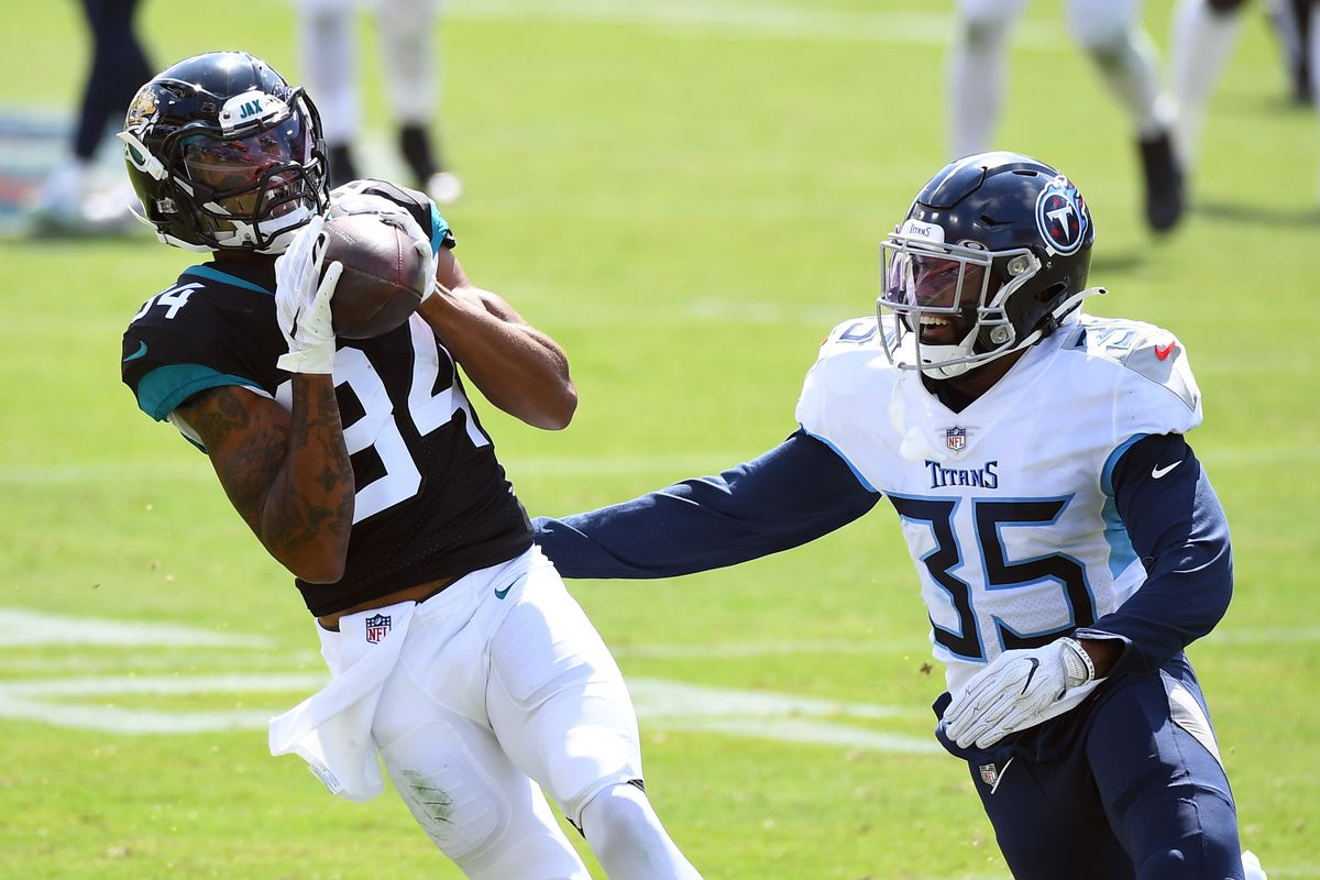 Jacksonville Jaguars wide receiver Keelan Cole  catches a pass in front of coverage from Tennessee Titans defensive back Chris Jackson  during the first half at Nissan Stadium