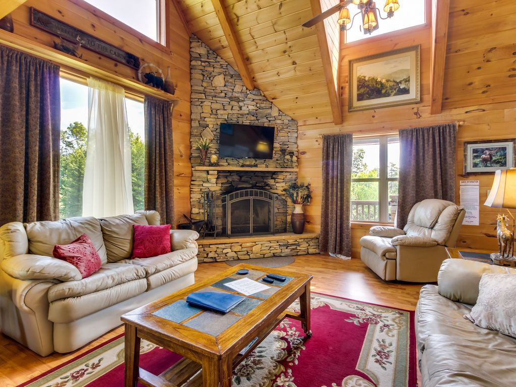 Large living room with vaulted ceiling, floor-to-ceiling stacked stone fireplace, couches, area rug, and coffee table.