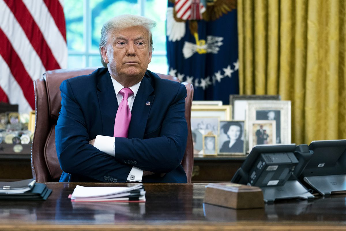 President Donald Trump sits behind the Oval Office desk with his arms crossed.