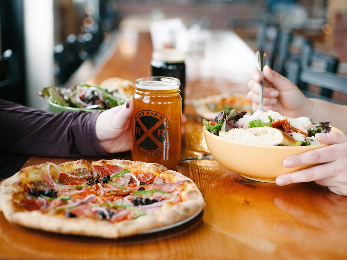 Two people (their faces aren't shown) eat at a wood table; one holds a mason jar filled with beer, the other is eating a salad, and there's a full pizza pie and between them covered in toppings.