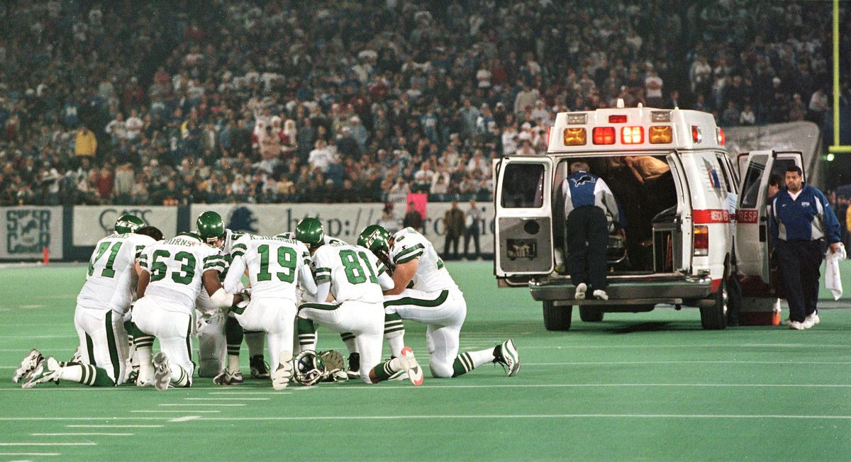 Members of the New York Jets kneel in a circle and
