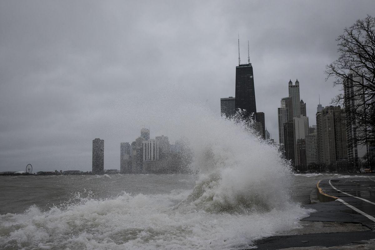 Waves from Lake Michigan crash against the lakefront trail near Oak Street Beach.