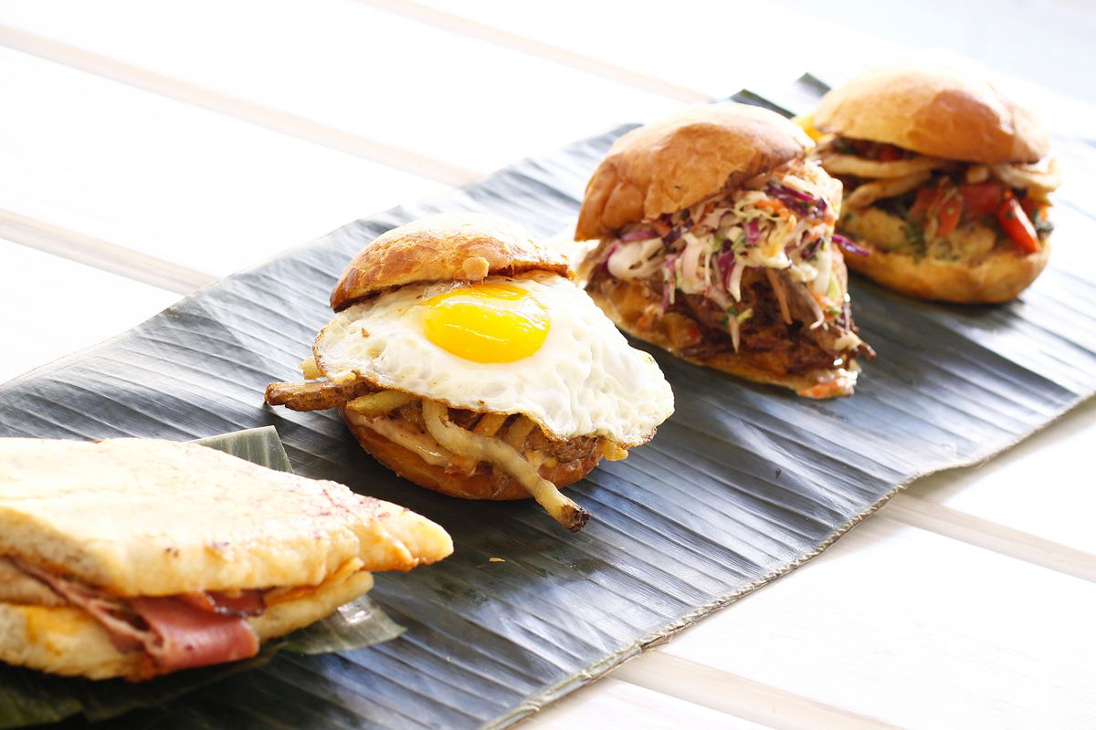 A row of sandwiches from Frita Batidos including an egg-topped burger with french fries and a Cubano sandwich.