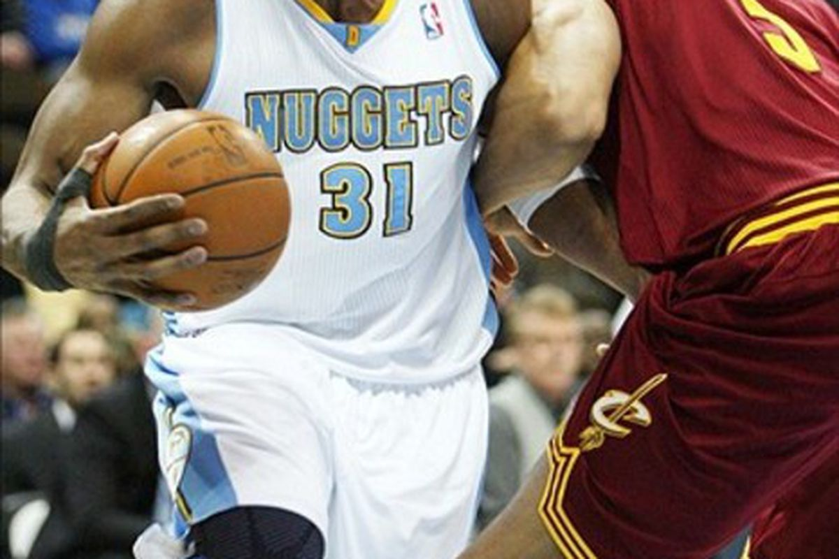 March 7, 2011; Denver, CO, USA; Denver Nuggets center Nene (31) drives the ball against Cleveland Cavilers center Ryan Hollins (5) during the first quarter at the Pepsi Center.  Mandatory Credit: Chris Humphreys-US PRESSWIRE