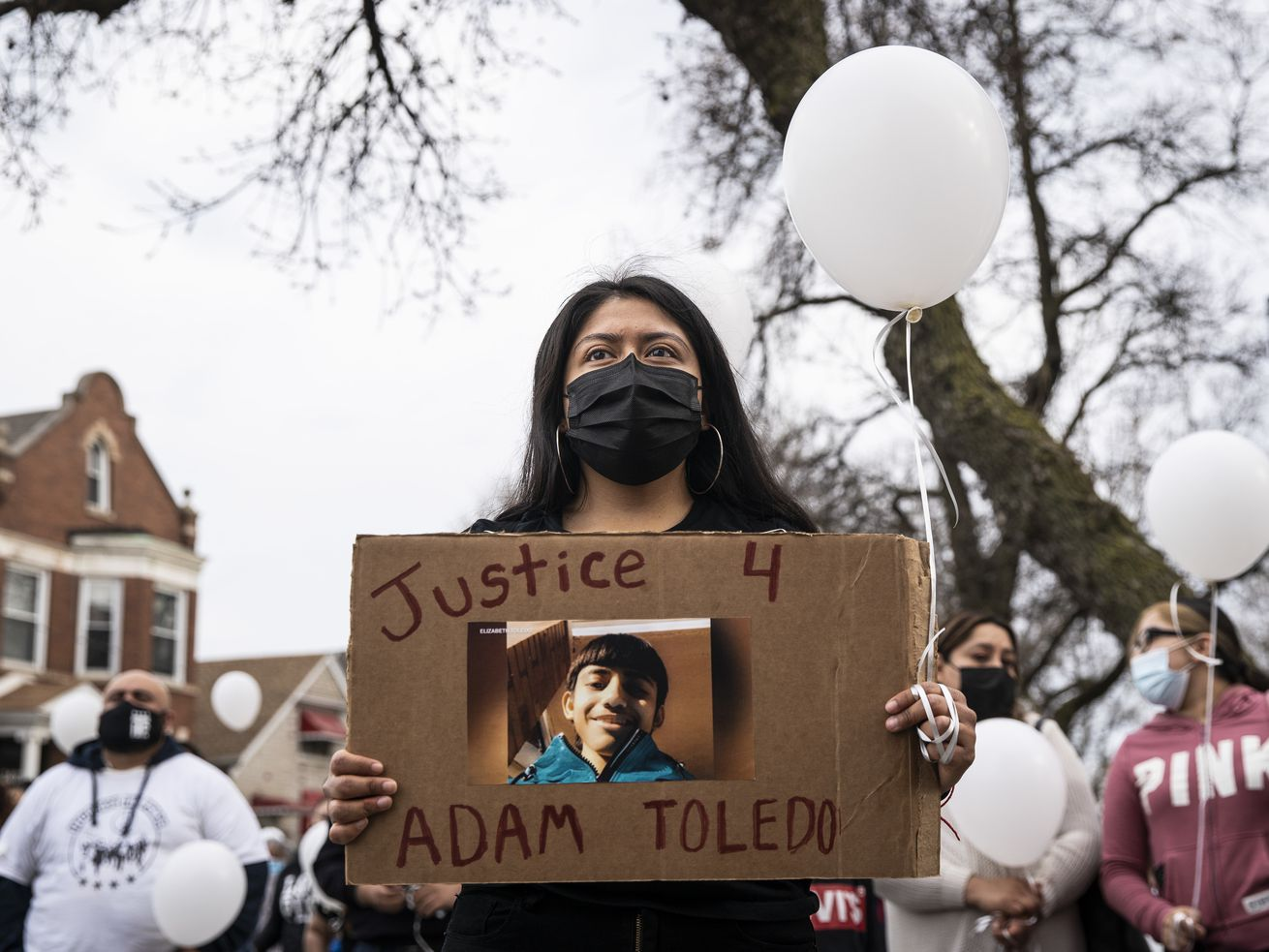 Ana Solano, 26, of Little Village, joins dozens Monday afternoon at a vigil for 13-year-old Adam Toledo near the location of the shooting at West 24th Street and South Sawyer Avenue in Little Village.