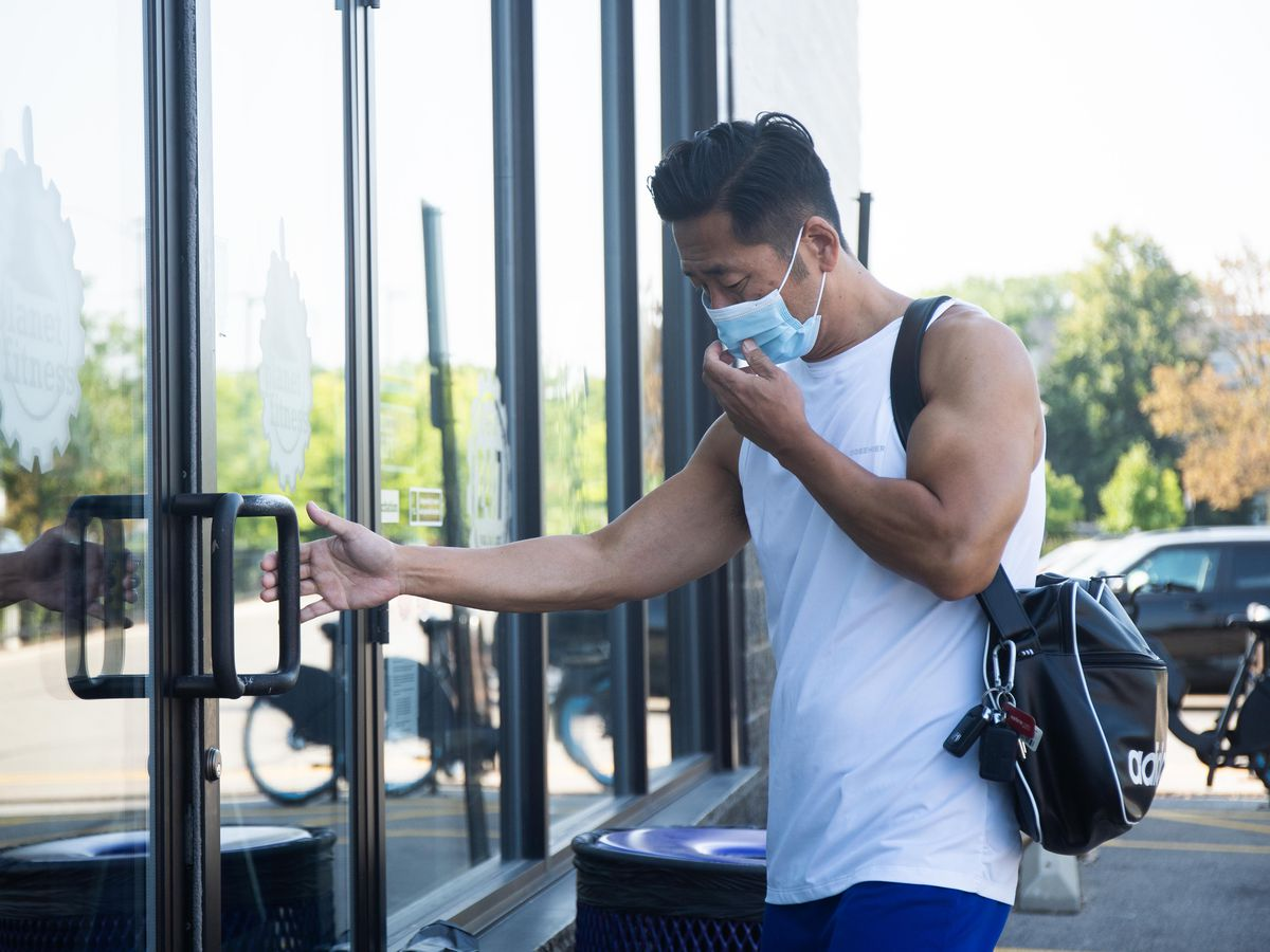 A man wearing a mask enters a Logan Square gym in August. After a surge in Delta variant cases, Illinois COVID-19 numbers are back down to the lowest levels seen since mid- August.