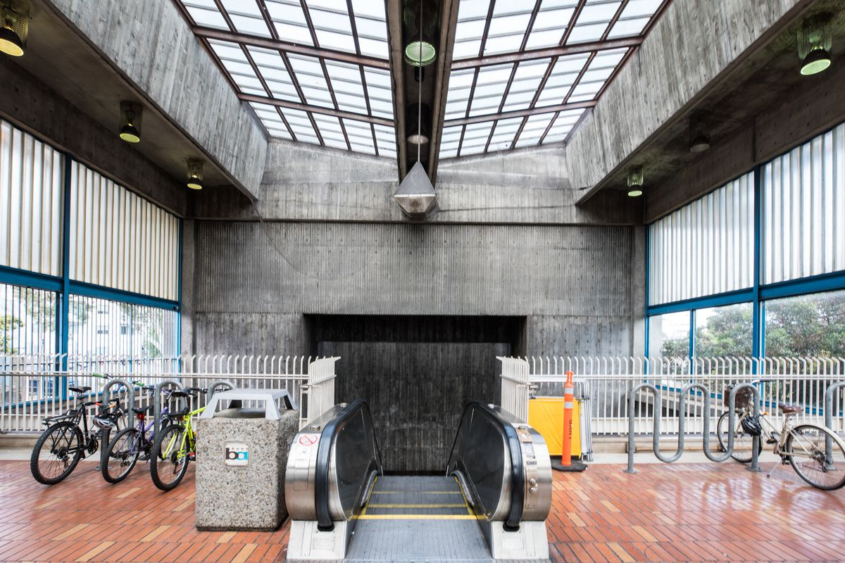 Inside a subway station with an escalator leading down towards the platform. On either side of the escalator are bike racks, while above is an inverted skylight, big windows, and a back concrete wall.