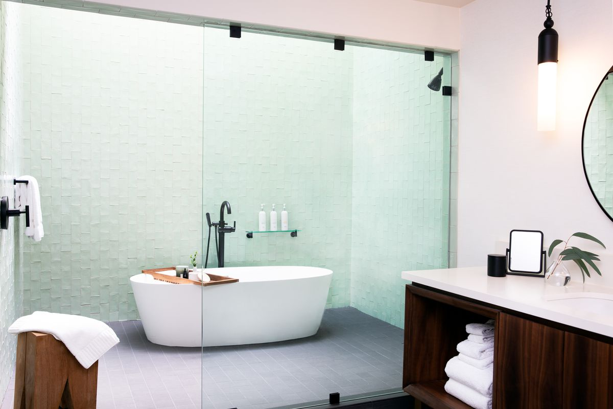 A large walk-in shower has light green tile and a standalone soaking tub inside it.