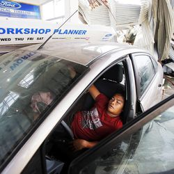 A man sleeps in a car in a damaged Ford dealership in Tacloban, Friday, Nov. 22, 2013.