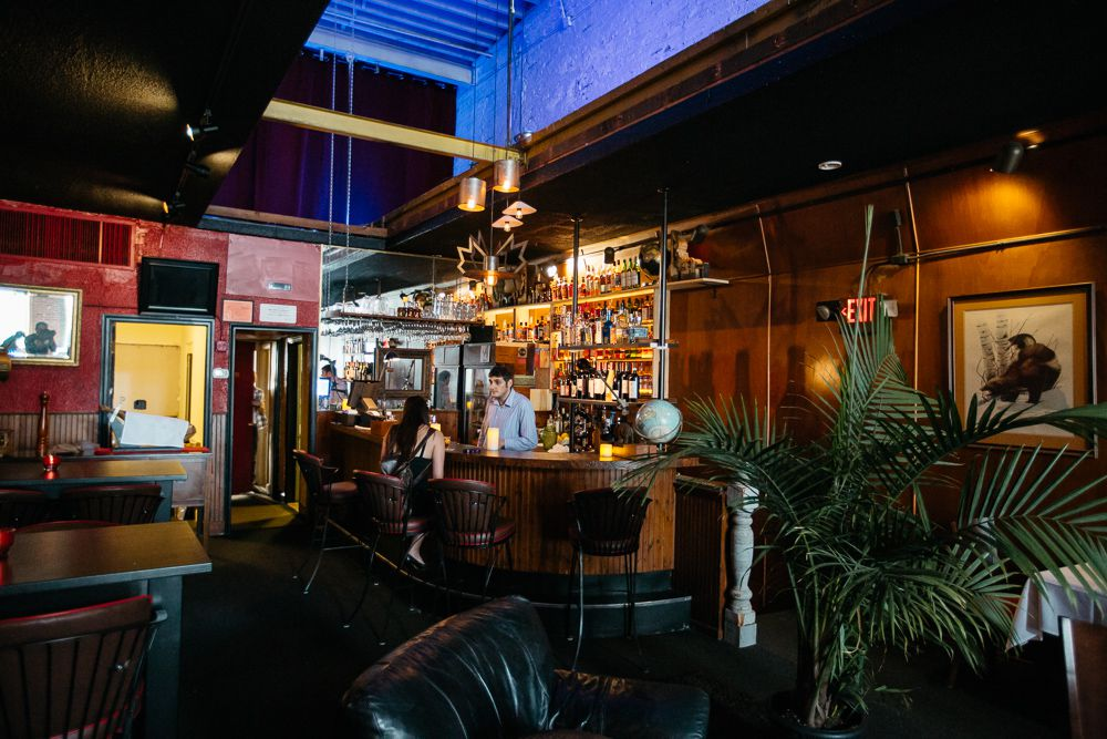 A dark wood bar surrounded by red walls and lots of green tropical plants.