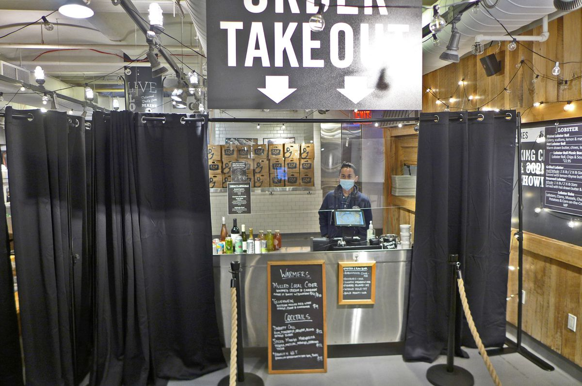 Two black curtains with a table in between, behind which stands a masked employee.