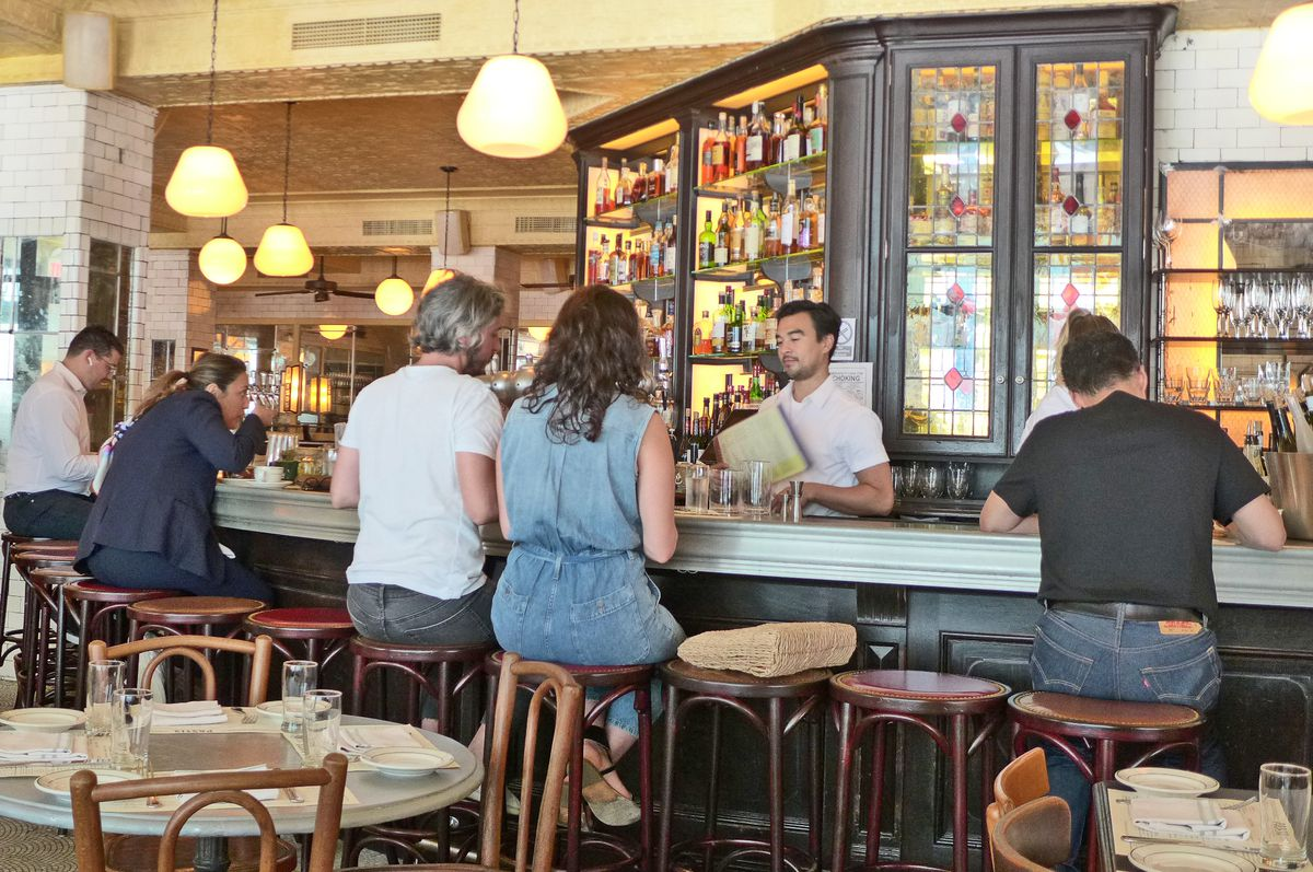 Several people sit on stools, their backs to us, at French brassserie Pastis...