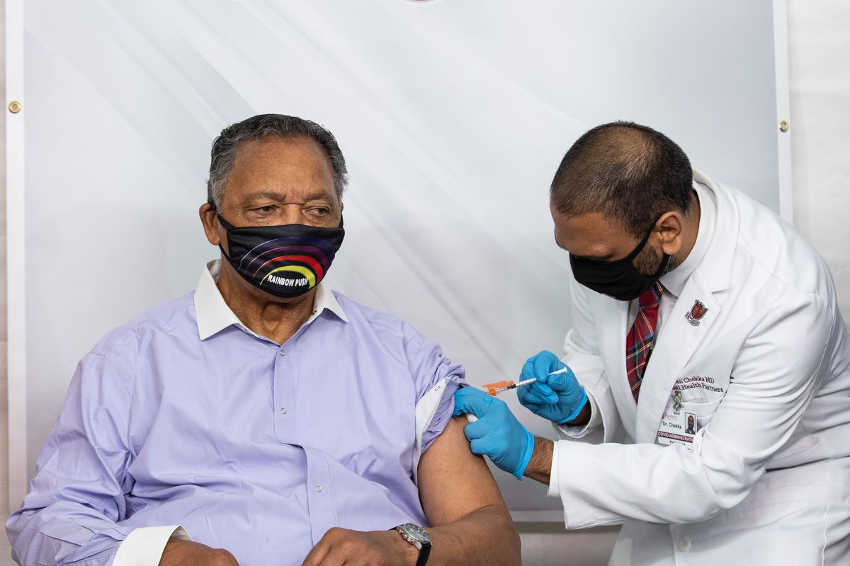 """Civil rights leader the Rev. Jesse Jackson receives a coronavirus vaccine from physician Kiran Chekka at Roseland Community Hospital Friday, part of efforts by Black community leaders to battle distrust of the vaccine in that community. Jackson was accompanied by Dr. Kizzmekia """"Kizzy"""" Corbett, the renowned Black immunologist who co-led the National Institutes of Health team that discovered the Moderna vaccine."""