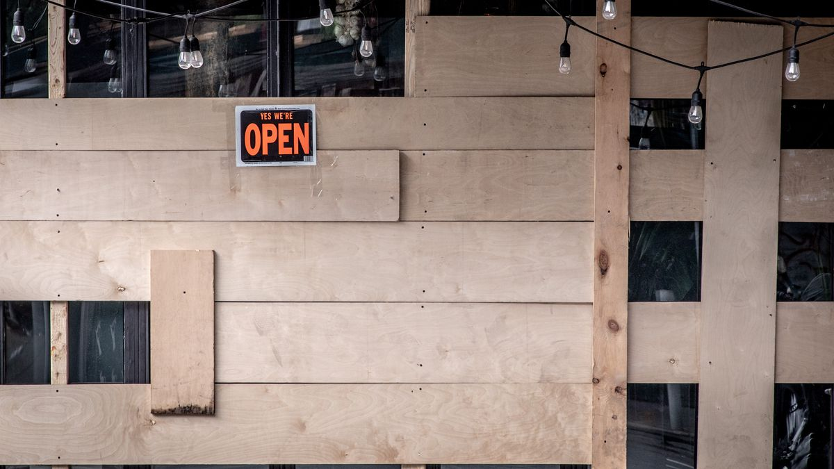 """A business with wooden boards across its window and market lights hanging from the ceiling. A sign posted to the boards says """"Open"""""""