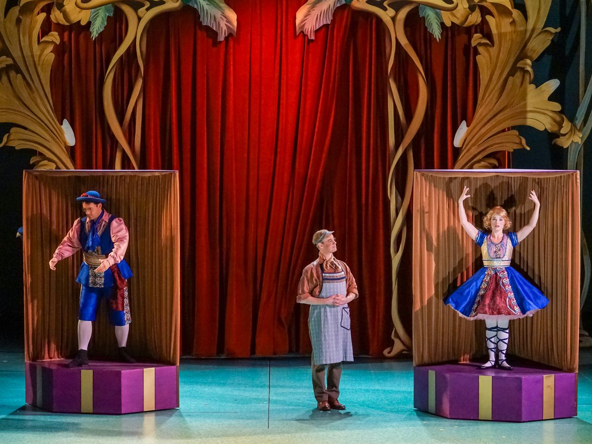 Three people on a blue stage. Two of the people are standing on colorful platforms. One person is standing between them. There is a red curtain with a decorative frame in the background.