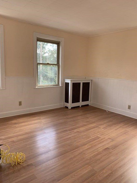 An empty room with a covered radiator and a window in the corner.