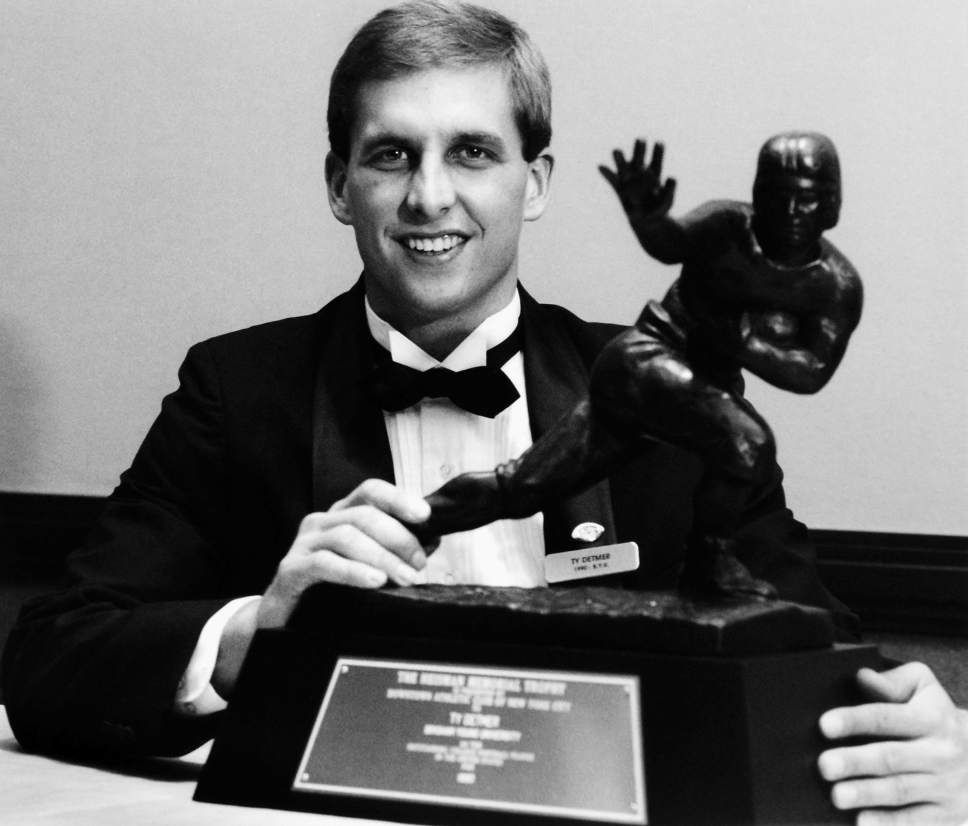 Ty Detmer is shown posing with the 1990 Heisman Trophy. The former Cougar quarterback great is now BYU's offensive coordinator.