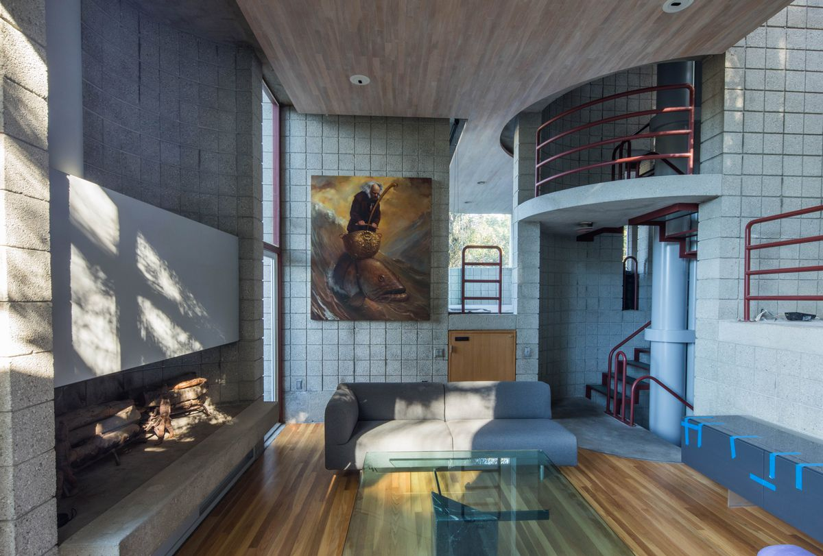 A large open room, double-height, with a huge fireplace along one wall. And open staircase winds behind the main living room area.