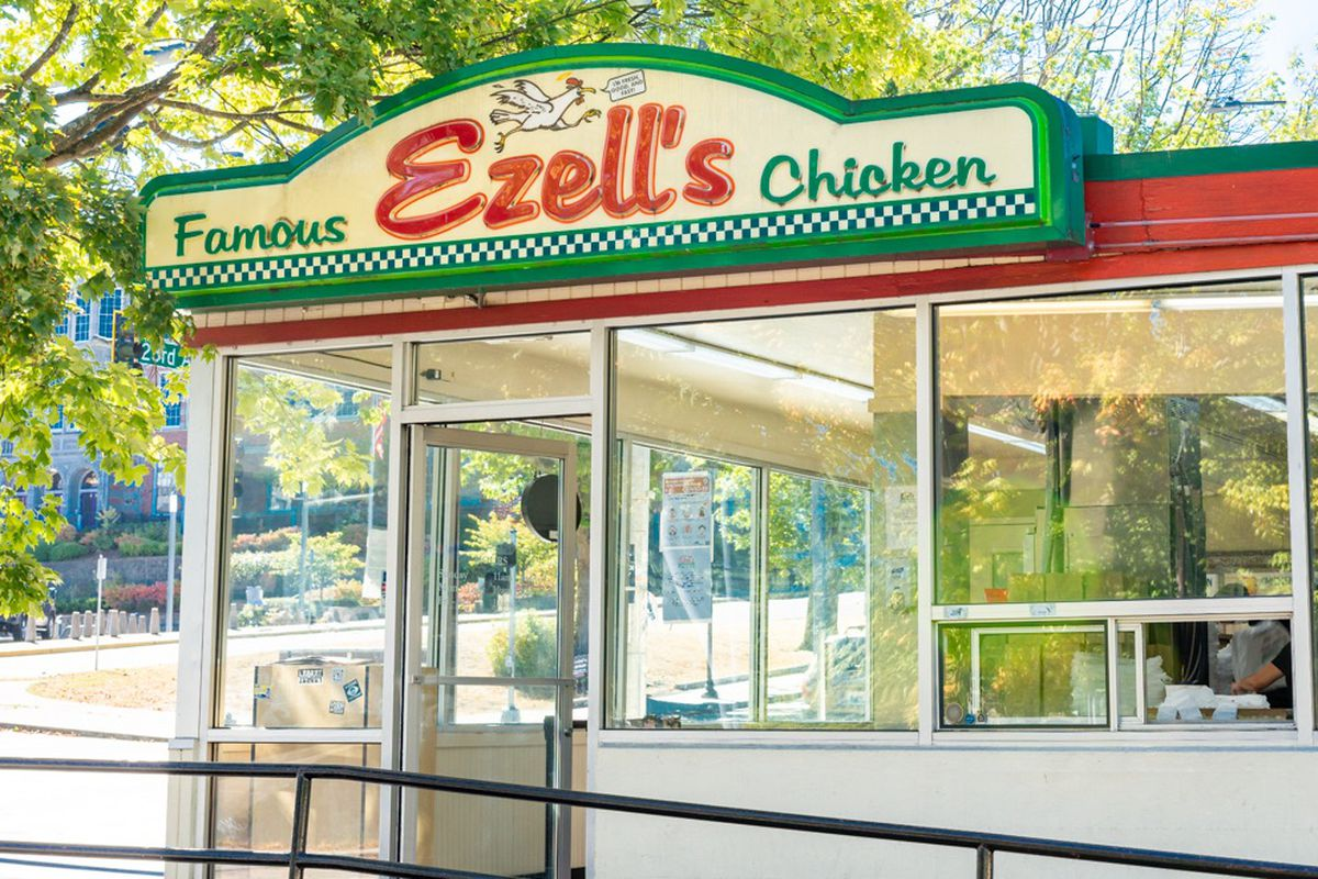 The storefront of Ezell's Famous Chicken on a sunny day, with the restaurant's famous red and green sign prominently displayed.
