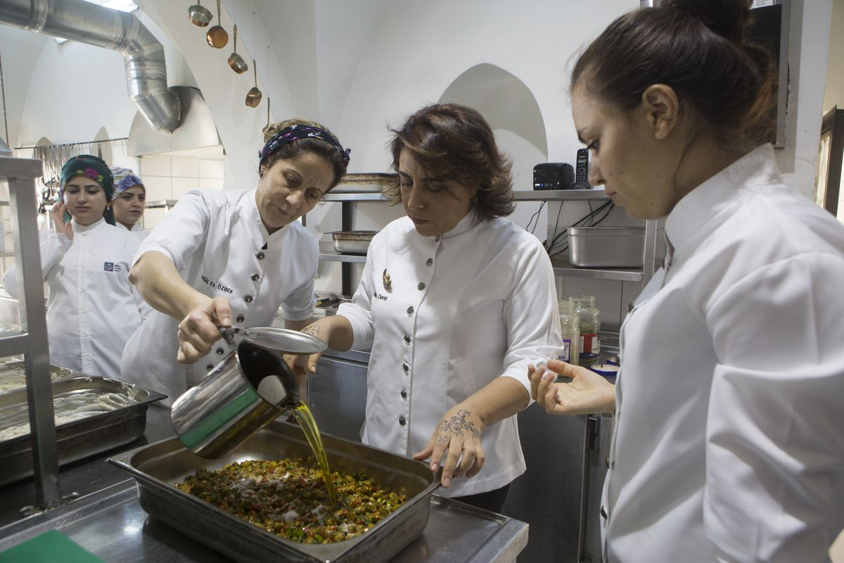 A woman pours olive oil into a dish as others look on