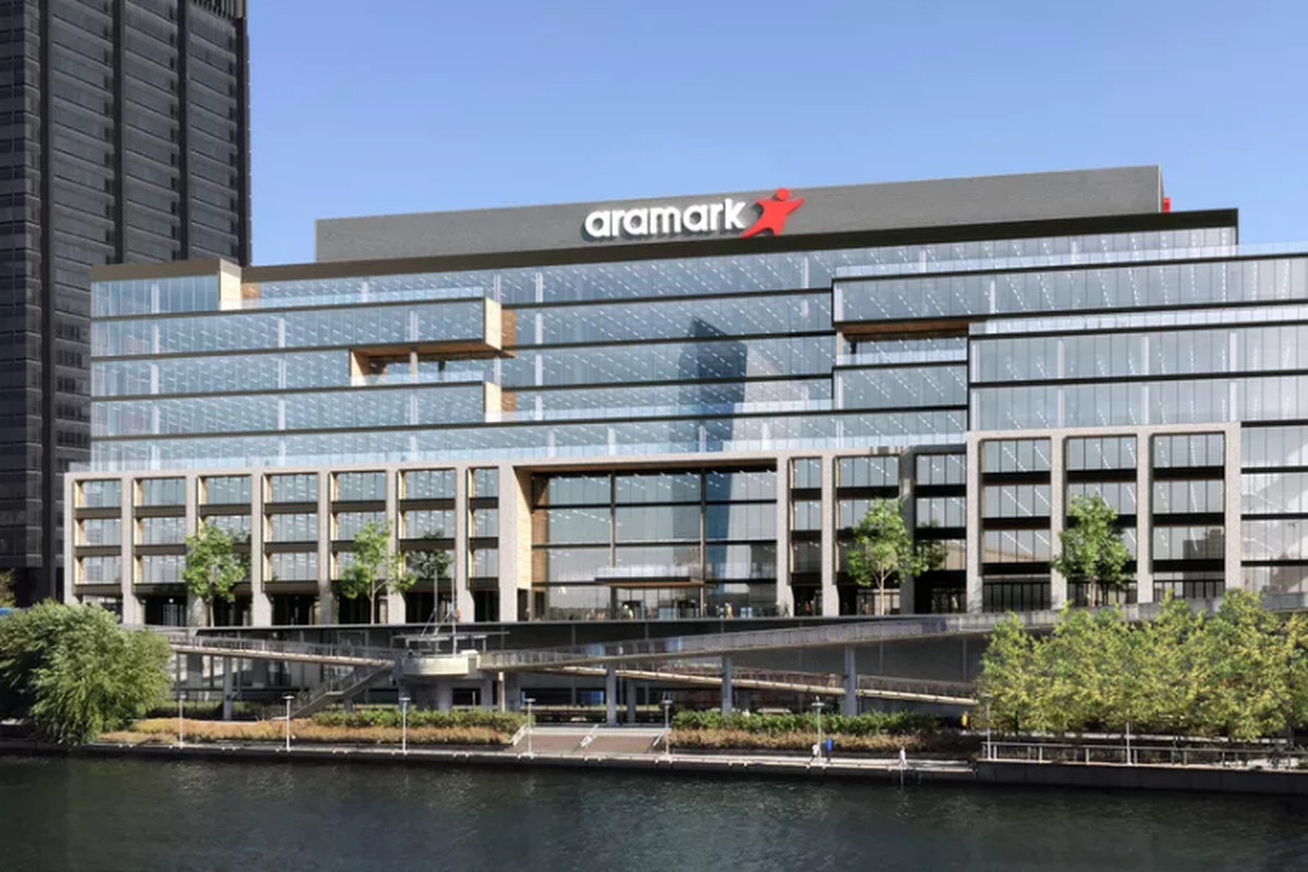 The exterior of 2400 Market Street in Philadelphia. The facade is glass. There are trees in front and a body of water. There is a sign on the building that reads: Aramark.