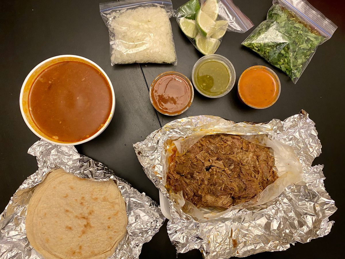 El Chaparro's barbacoa, with tortillas, consomé, three salsas, onions, cilantro, and lime wedges