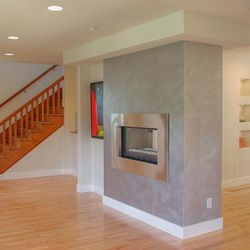 This home was renovated with modern flair. It now has a metallic, see-through fireplace; clean, open space; and a lot of natural light.