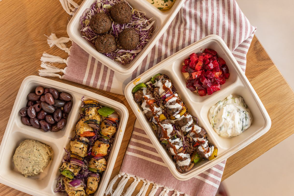 Several takeaway boxes of Middle Eastern casual food.