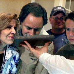 Mary and Steve Ponnath of Kansas City and Ian Beyer, far right, of Salt Lake City, smell a brick of tea that dates back to the Boston Tea Party era at the Independence Through History Museum in the Grand America in Salt Lake City on Friday, July 5, 2013.