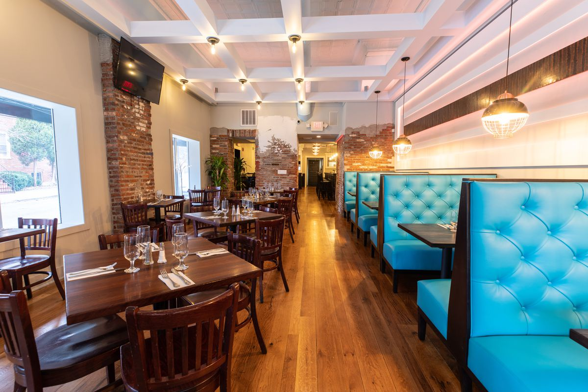 interior of restaurant with blue booths and wood tables