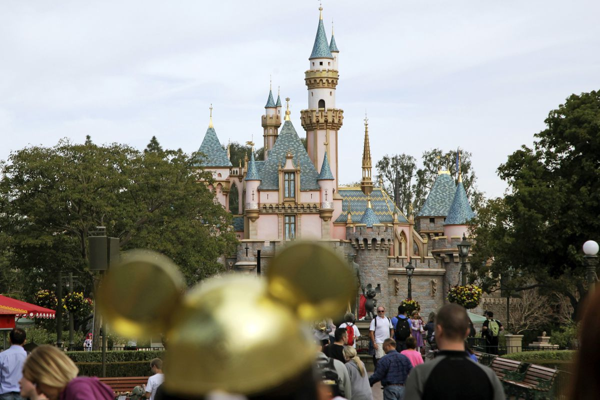 """In this Jan. 22, 2015, file photo, visitors walk toward Sleeping Beauty's Castle in the background at Disneyland Resort in Anaheim, Calif. Prosecutors believe there may have been """"felony conduct"""" during a recent Disneyland brawl which was videotaped and w"""