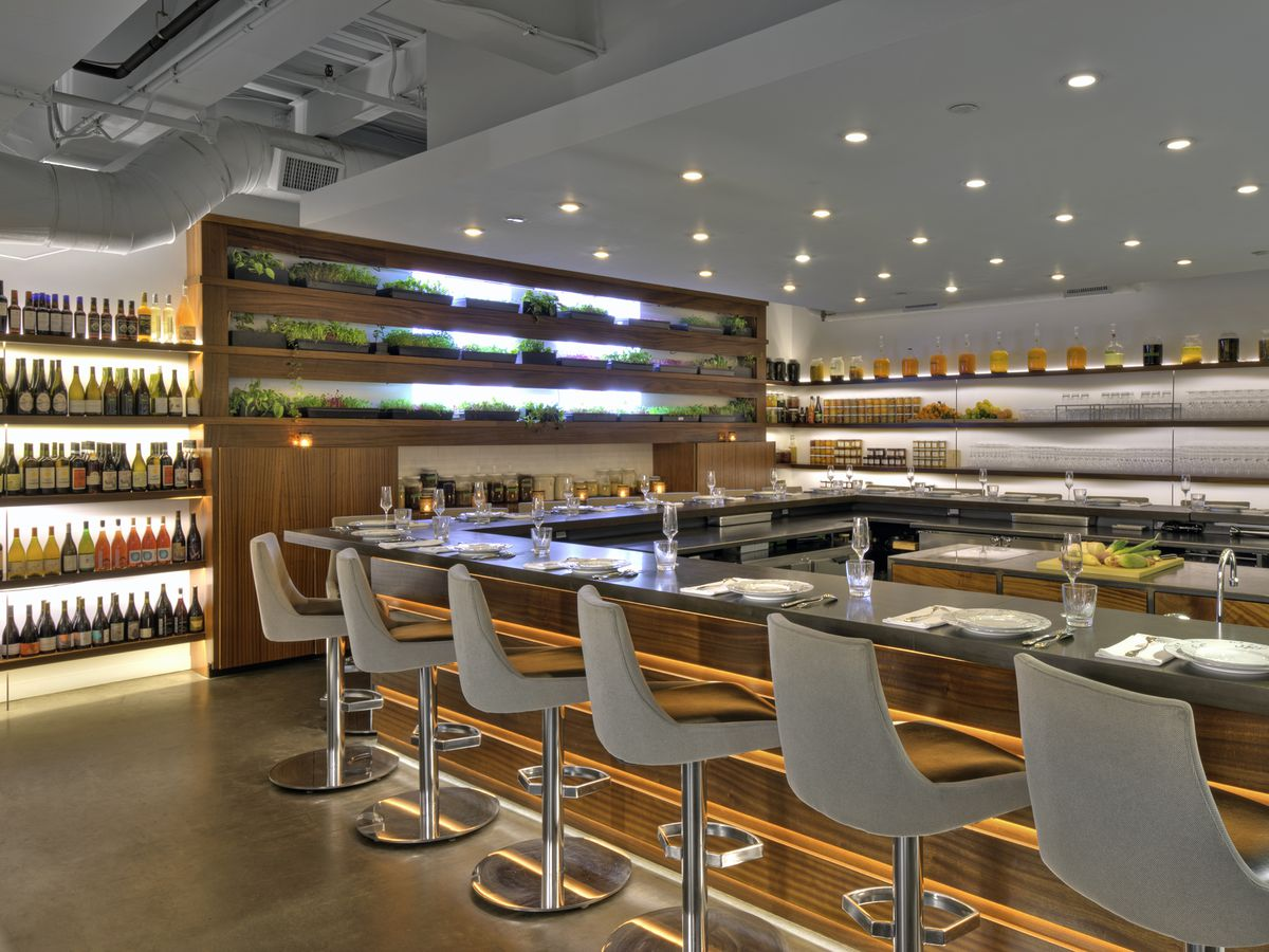 A restaurant interior features a sleek bar, white and light wood accents, and shelves of wine. There are also herbs growing on shelves in front of a window.