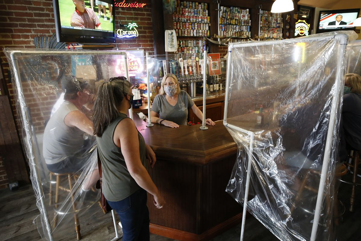 Woman wears mask behind a bar. In the front of the bar are two screens made of plastic and piping.