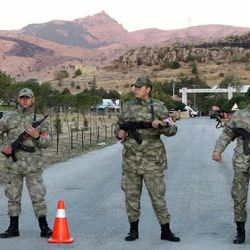 Soldiers stand near the site hours after an explosion at an ammunition store in Afyonkarahisar in western Turkey whcih killed some 25 soldiers and wounded at least four others, Thursday, Sept. 6, 2012. The blast happened on Wednesday night at a military storage for hand grenades in Afyon, military said. Environment Minister Veysel Eroglu said the explosion was most likely caused by an accident and certainly not as a result of terrorism. It is thought many of the soldiers were trapped inside the building as firefighters tackled the huge blaze.(AP Photo)