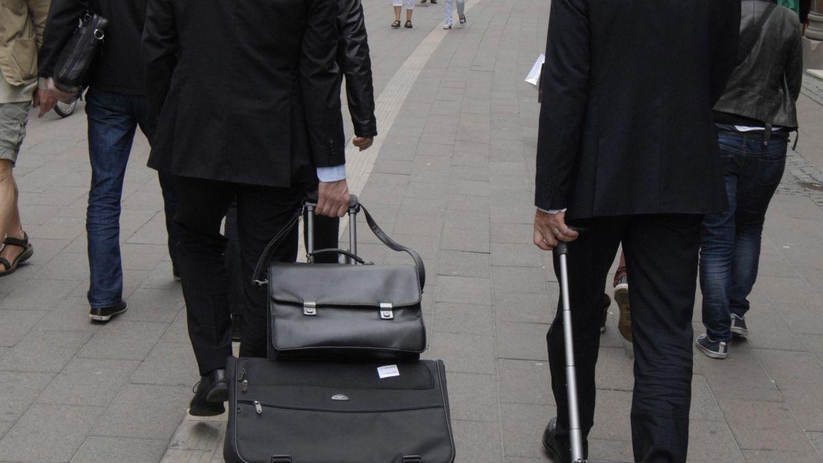Businessmen with roller suitcases navigate a street in Copenhagen.
