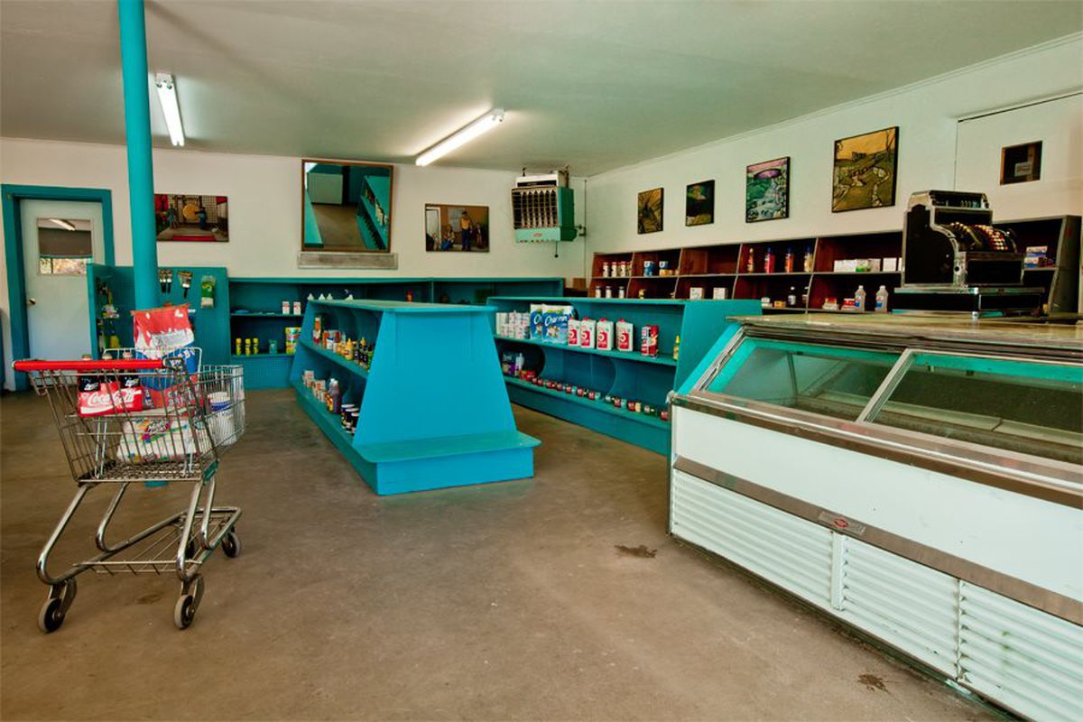 The interior of an old-fashioned general store featuring turquoise-painted display cases and shelves, raw concrete floor, fluorescent lights, and a deli case.