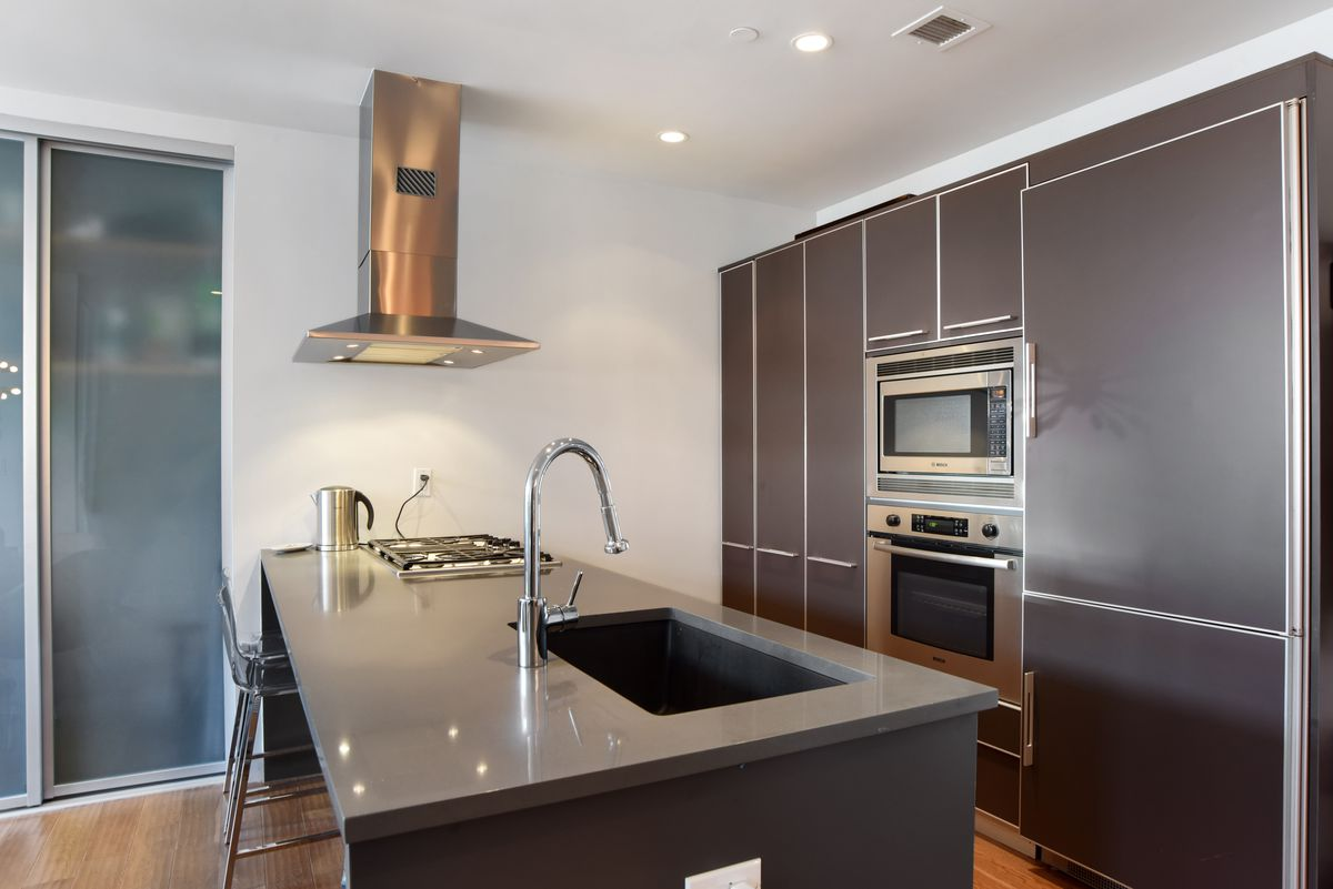 A kitchen with dark grey cabinetry and a large island.
