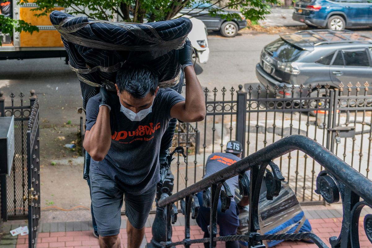 Marcos Rodríguez carries a chair up the stoop and into Coerbell and Patton's new home in a Brooklyn brownstone, Aug. 14, 2020.