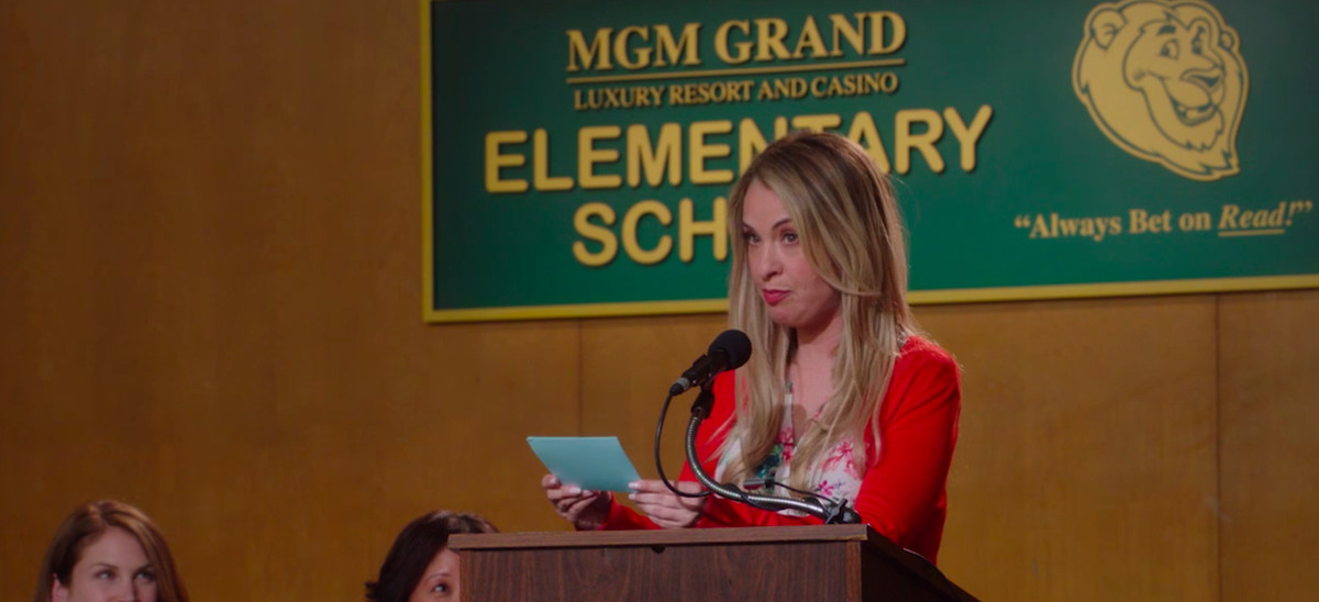 """A blond woman speaking at a lectern in front of a sign that reads: MGM Grand Luxury Resort and Casino Elementary School. """"Always Bet on Read!"""""""