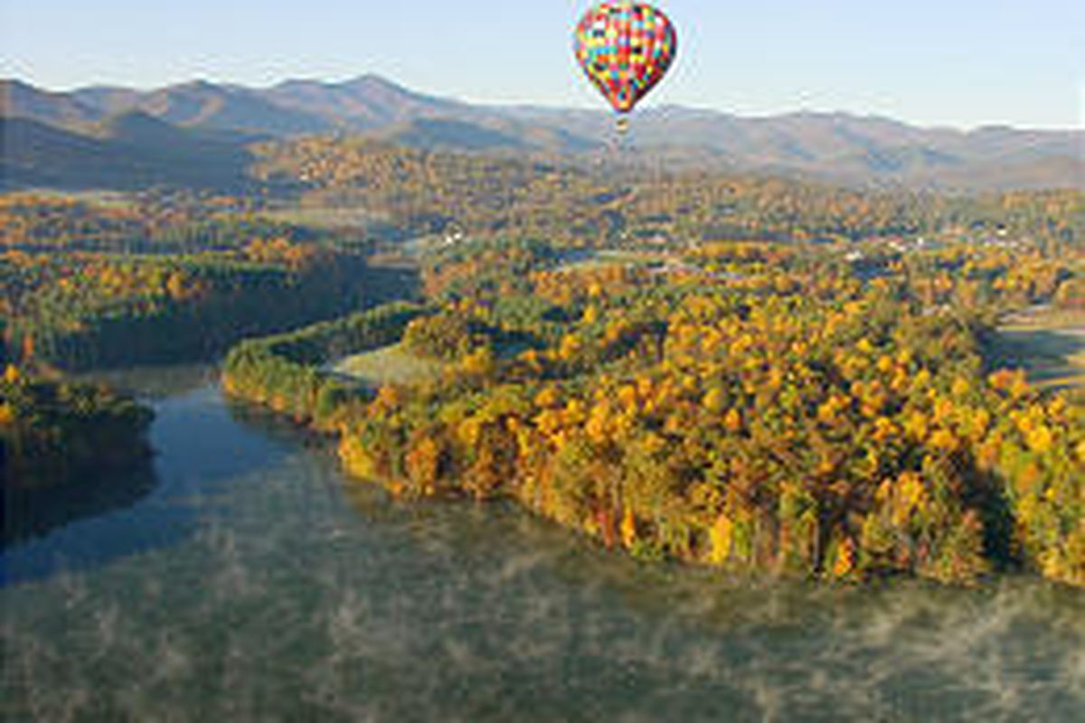 For a bird's-eye view of fall foliage, consider a balloon ride. Above, a hot air balloon soars over Enka Lake in South Asheville, N.C., with Mount Pisgah and the Blue Ridge Mountains in the background.
