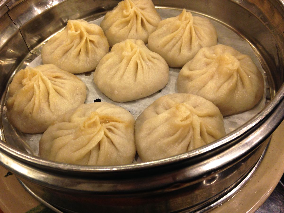A metal steamer containing eight plump Chinese soup dumplings