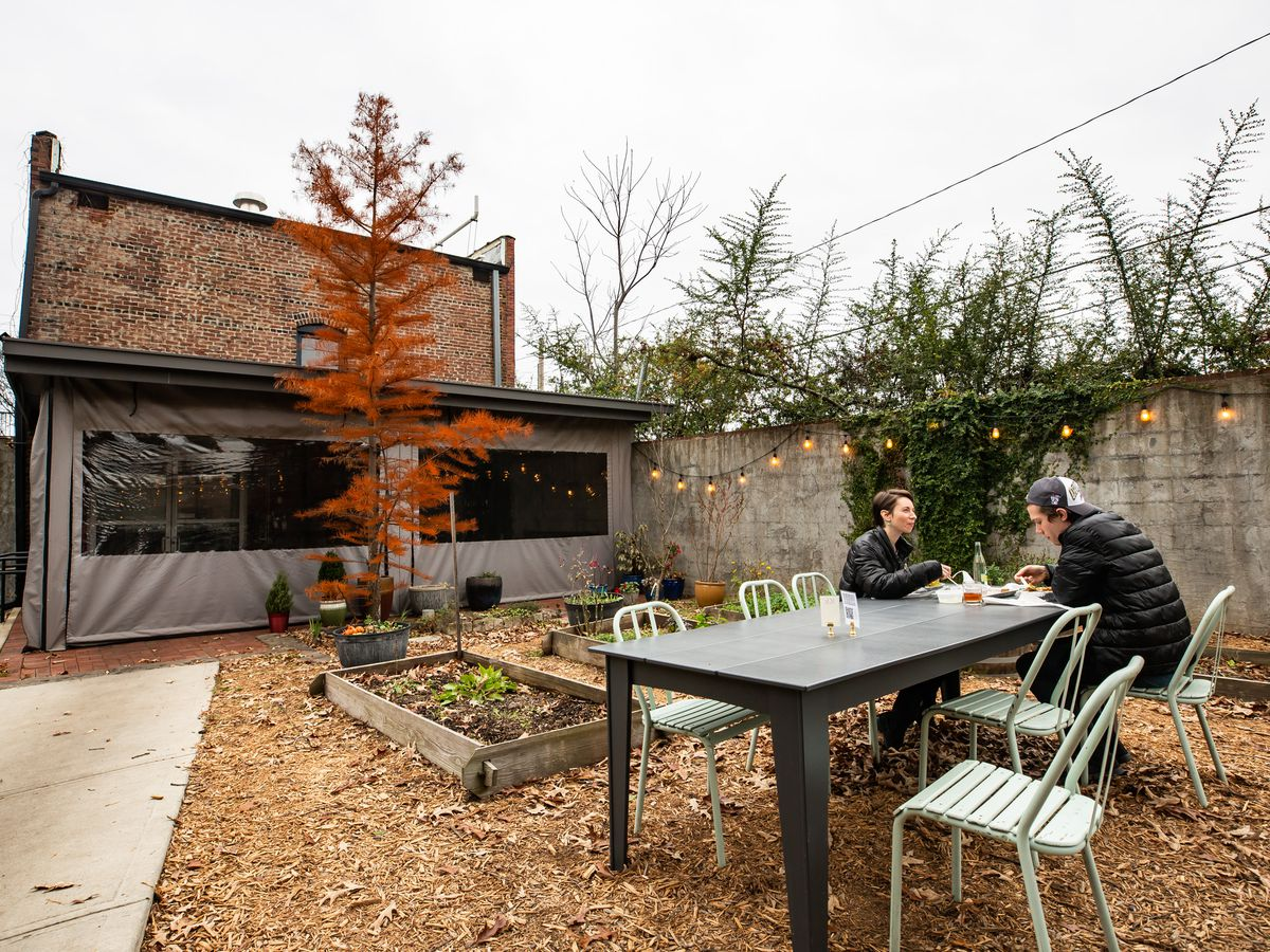 Staplehouse Market's outdoor garden patio with covered seating on the porch. the porch is enclosed for the winter