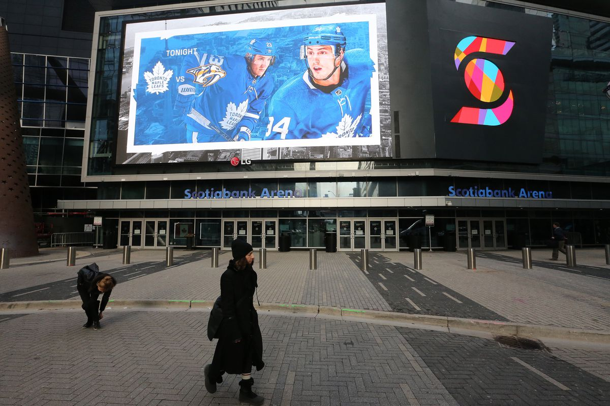 fans and commuters walk past Scotiabank Arena where the Toronto Maple Leafs and the Nashville Predators were supposed to play tonight. The NHL along with the NBA, MLB, NLS and MLS have suspended all games in order to slow the spread of COVID-19