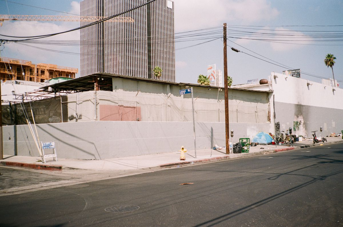 The corner of a street, next to a broken down building, and the sidewalk has a tent being used by a homeless man, a bicycle and other various items. A high rise building looms in the background.